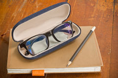Glasses on notebook. On wood background Royalty Free Stock Image
