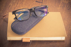 Glasses on notebook. On wood background Royalty Free Stock Images