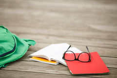 Glasses with notebooks and backpack closeup. On wooden surface.school accessories Stock Photography