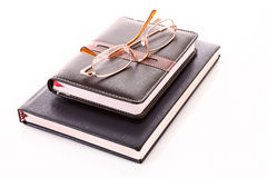 Glasses on notebooks isolated Stock Photography