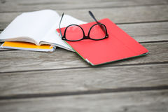 Glasses and notebooks on wooden floor. Glasses and notebooks lie on wooden floor.Accessories for student.Accessories for student Royalty Free Stock Images