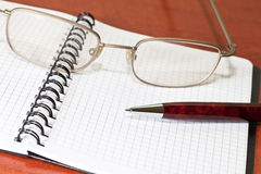 Glasses, notepad with pen Royalty Free Stock Photos