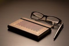 Glasses, notepad, pen on a table Royalty Free Stock Photography