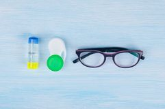 Glasses and objects for cleaning and storing contact lenses, to improve vision, on a blue background royalty free stock photos