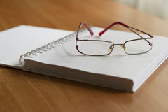 Glasses and office supplies. Closeup, soft focus, focus on glasses Stock Image