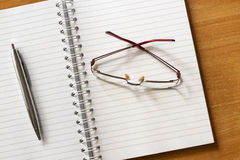Glasses and office supplies. Notebook and pen Royalty Free Stock Photography