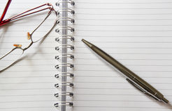 Glasses and office supplies. Notebook and pen Stock Photos