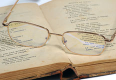 Glasses and old book. On a white background Royalty Free Stock Photos