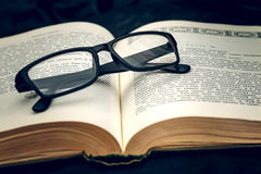 Glasses on old book. Black glasses lying on the open page of an old book Stock Photo