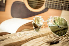 Glasses with old book and guitar on old wooden table Stock Images