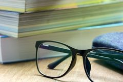 Glasses and old books stacked. Glasses and old books stacked on brown wood background in the morning light royalty free stock photos