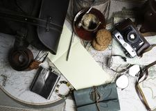 Still life in style of flat lay of travel items. Glasses, old film camera watch and other items of travel on the table royalty free stock photography