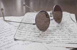 Glasses on old letters. Round glasses on old letters Royalty Free Stock Images