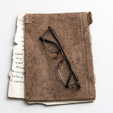Glasses and old notebook on table Stock Image