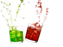 Glasses of olourful cold drinks with water splash and ice cubes. Royalty Free Stock Photography