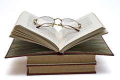 Glasses on an open book. Some books and a pair of glasses isolated on a white background Stock Photos