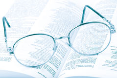 Glasses on the open book. In blue tones Royalty Free Stock Image
