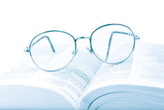 Glasses on the open book. In blue tones Royalty Free Stock Photo