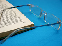 Glasses and open book. Pair of glasses on page of open book with blue background Royalty Free Stock Photos