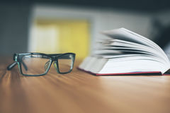 Glasses and open book. Closeup of glasses and open book on wooden desktop. Knowledge concept Stock Photo