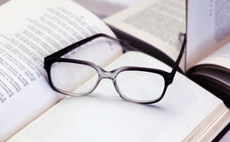Glasses and open books on the table Royalty Free Stock Photo