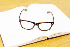 Glasses on open empty book Royalty Free Stock Photo