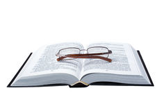 Glasses on the opened book. The opened book on which glasses lay, is isolated, on a white background Stock Images