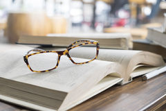 Glasses on opening book in library or cafe. Stock Photography