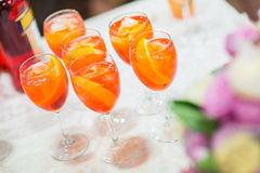 Glasses with orange cocktail on a festive table. Glasses with cold tropical cocktails and orange slices on a summer table royalty free stock photography