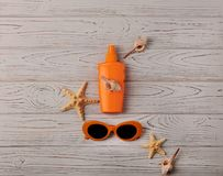 Glasses of orange color and sunscreen on a wooden background. Selective focus Stock Image