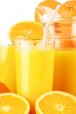 Glasses of orange juice and fruits on white Royalty Free Stock Photos