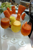 Glasses with organic juices. Glasses with carrot and pineapple juices at the restaurant Royalty Free Stock Photos