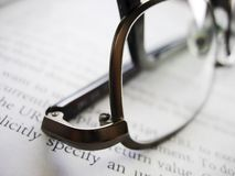 Glasses over a book. A pair of glasses over an open book Stock Image