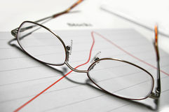 Glasses over graphs. Glasses over stock graphs royalty free stock photos