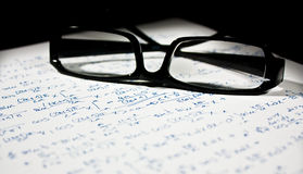 Glasses over a math sheet. Isolated on a black background Stock Photo