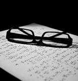 Glasses over a math sheet. Isolated on a black background Stock Images
