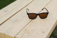 Glasses on a park bench. retro vintage. Sunglasses on a wooden bench Royalty Free Stock Photography