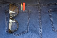 Glasses pen in back blue jeans. Glasses pencil and pen in back blue jeans pocket denim background texture Stock Image