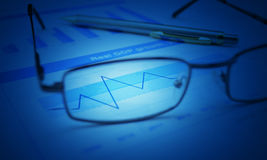 Glasses and pen on blue financial chart and graph, blue tone, su Stock Photography