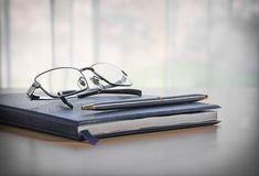 Glasses and pen on a book Stock Images