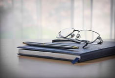 Glasses and pen on a book Royalty Free Stock Photo