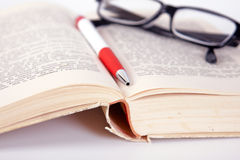 Glasses and pen on the book Stock Photos