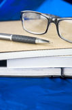 Glasses and pen on books Stock Photo