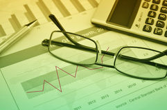 Glasses, pen and calculator on financial chart and graph Stock Photography