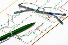 Glasses and pen on chart Stock Images