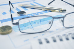 Glasses, pen and coin on blue financial chart and graph, success. Glasses and pen on blue financial chart and graph, success concept Royalty Free Stock Photos