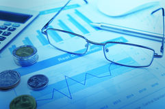 Glasses, pen and coin on growth financial graph, accounting back Stock Image