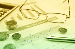 Glasses, pen and coin on growth financial graph Stock Photo