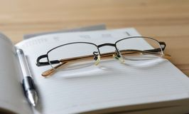 Glasses and pen on diary Royalty Free Stock Photos