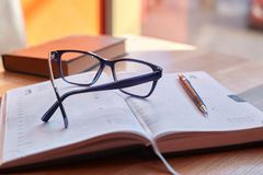 Glasses and a pen on a diary Royalty Free Stock Photography